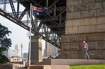Sydney  Australien  Mann steht neben einer australischen Flagge unter der Sydney Harbour Bridge