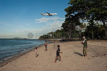 Singapur  Republik Singapur  Menschen geniessen einen Tag am Strand waehrend im Hintergrund ein Flugzeug den Flughafen Changi anfliegt