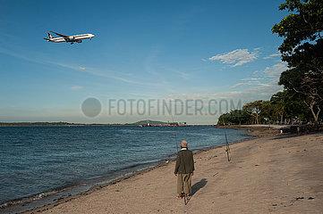 Singapur  Republik Singapur  Mann steht am Strand des Changi Beach Parks und beobachtet ein Flugzeug beim Landeanflug