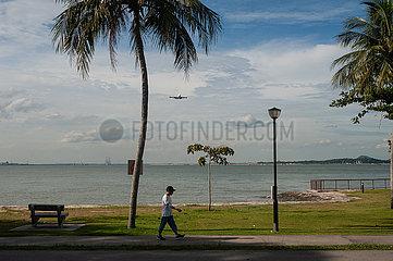 Singapur  Republik Singapur  Mann geht am Ufer des Changi Beach Parks entlang waehrend sich ein Flugzeug naehert