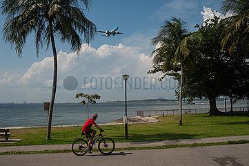 Singapur  Republik Singapur  Fahrradfahrer faehrt am Ufer des Changi Beach Parks entlang waehrend sich ein Flugzeug naehert