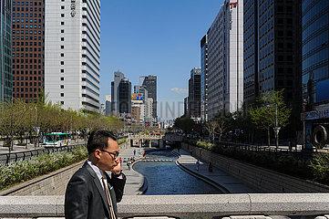 Seoul  Suedkorea  Mann telefoniert waehrend im Hintergrund der Cheonggyecheon Wasserlauf entlang fliesst