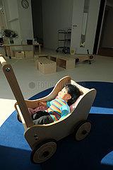 Deutschland  Bremen - Puppe in einem Kinderwagen aus Holz in einer neu eroeffneten Kindertagesstaette