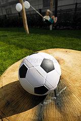 Deutschland  Bremen - Fussball aus Gummi auf dem Gelaende einer Kindertagesstaette  hinten Maedchen auf der Schaukel