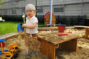 Deutschland  Bremen - Junge in der Sandkiste einer Kindertagesstaette