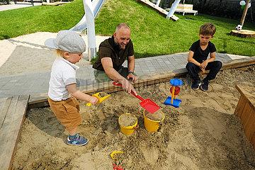 Deutschland  Bremen - Eroeffnung einer Kindertagesstaette: Vater spielt mit seinem Sohn in der Sandkiste  der aeltere Bruder sitzt daneben