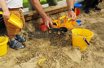 Deutschland  Bremen - Sandkiste einer Kindertagesstaette  Junge mit Betreuung