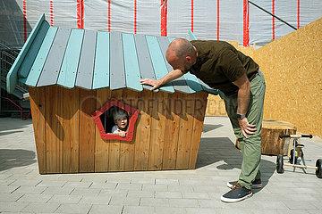 Deutschland  Bremen - Eroeffnung einer Kindertagesstaette: Vater spielt mit seinem Sohn