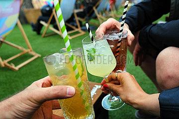 Deutschland  Oldenburg - 3 Freunde beim Anstossen mit Cocktails in einer Strandbar