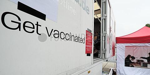 Deutschland  Bremen - Vom DRK betriebenes  mobiles Impfzentrum (Impfmobil) im Stadtteil Huckelriede. Englischsprachiger Slogan GET VACCINATED  rechts die Registrierung