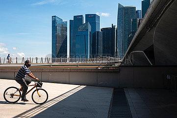 Singapur  Republik Singapur  Fahrradfahrer mit Mundschutz in Marina Bay mit dem Geschaeftszentrum im Hintergrund