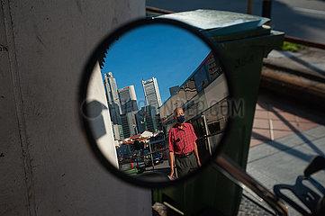 Singapur  Republik Singapur  Mann mit Mundschutz geht eine Strasse entlang und spiegelt sich dabei in einem Rueckspiegel