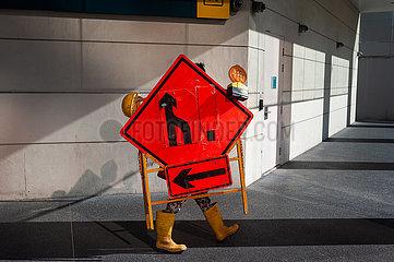 Singapur  Republik Singapur  Arbeiter traegt ein Strassenschild mit Warnlichtern im Stadtzentrum