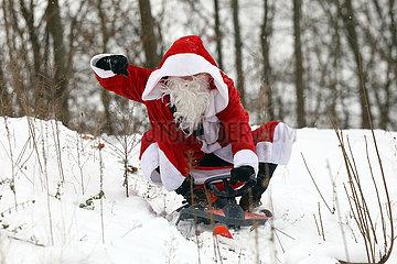 Berlin  Deutschland  Weihnachtsmann faehrt auf einem Schlitten einen Hang hinunter