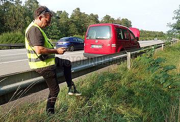 Ziesar  Deutschland  Mann sitzt bei einer Autopanne auf der A2 auf der Leitplanke und schaut auf sein Mobiltelefon