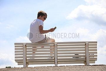 Hannover  Deutschland  junger Mann sitzt auf der Lehne einer Parkbank und schaut auf sein Mobiltelefon