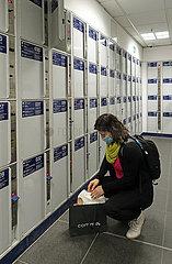 Berlin  Deutschland  Frau hockt in der Gepaeckaufbewahrung im Hauptbahnhof vor den Schliessfaechern