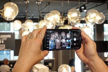 Berlin  Deutschland  Deckenleuchten aus dem Palast der Republik werden mit einem Smartphone fotografiert