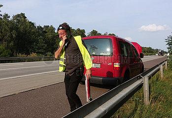 Ziesar  Deutschland  Mann mit zusammengefaltetem Warndreieck telefoniert nach einer Autopanne auf der A2
